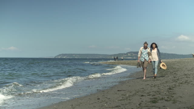 a mid adult couple walking on a beach - 35 39 jahre stock-videos und b-roll-filmmaterial
