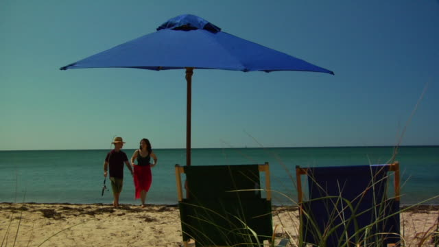 ms, mid adult couple walking on beach and sitting on chairs under sun umbrella north truro, massachusetts, usa - mid adult couple stock videos & royalty-free footage