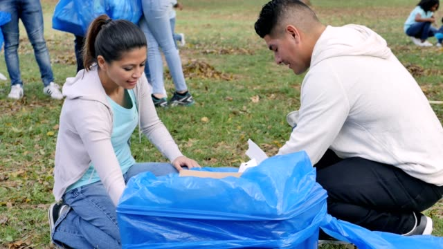 mid adult couple work together during community cleanup day - servizio sociale video stock e b–roll
