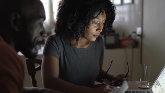 中期成人カップル勤務/自宅で手形を支払う - 税金点の映像素材/bロール