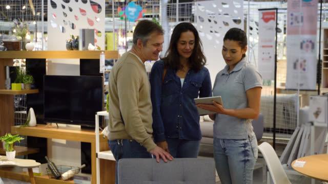 vidéos et rushes de couples de client adulte moyen avec la vendeuse à un magasin de meubles demandant au sujet d'une chaise tandis qu'elle tient une tablette - métier de la vente