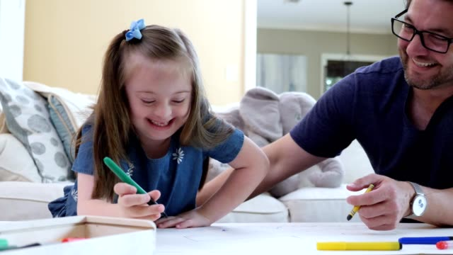mid adult dad enjoys coloring with special needs daughter - terapia alternativa video stock e b–roll