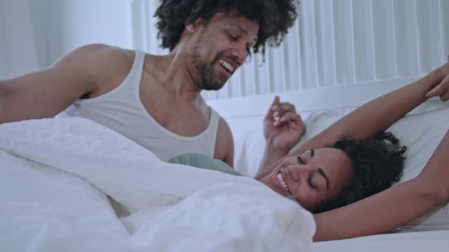 mid adult dark-skinned cool love couple waking up together peacefully at home in white bed in the early morning, he waked her up, she is stretching and yawning. - spanking stock videos and b-roll footage