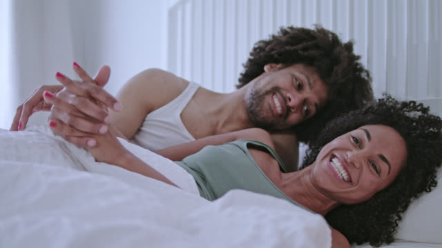 stockvideo's en b-roll-footage met mid adult dark-skinned love couple at home in white bed having a great time together on a weekend. - dubbel bed