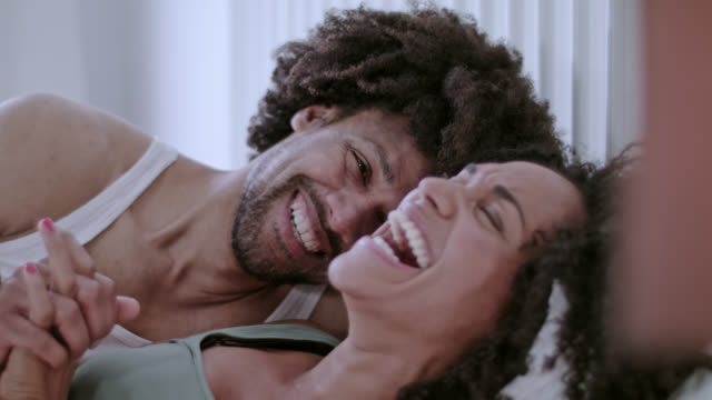 Mid adult dark-skinned love couple happy at home in white bed on a weekend having great fun together.