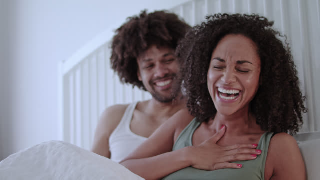 stockvideo's en b-roll-footage met mid adult dark-skinned love couple happy together at home in white bed on a weekend having great fun together. - dubbel bed