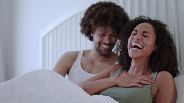 Mid adult dark-skinned love couple happy together at home in white bed on a weekend while having great fun together staying in bed.