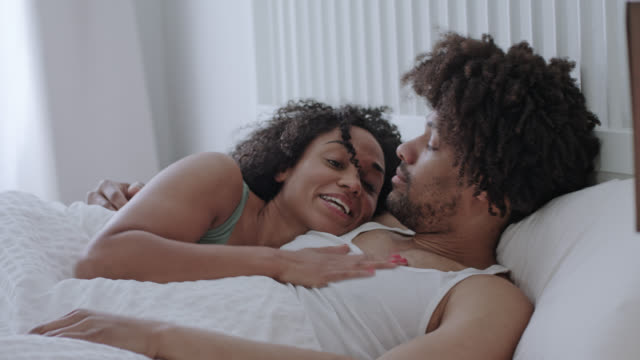 stockvideo's en b-roll-footage met mid adult dark-skinned love couple happy together at home in white bed on a weekend, she motivates him to get up. - dubbel bed