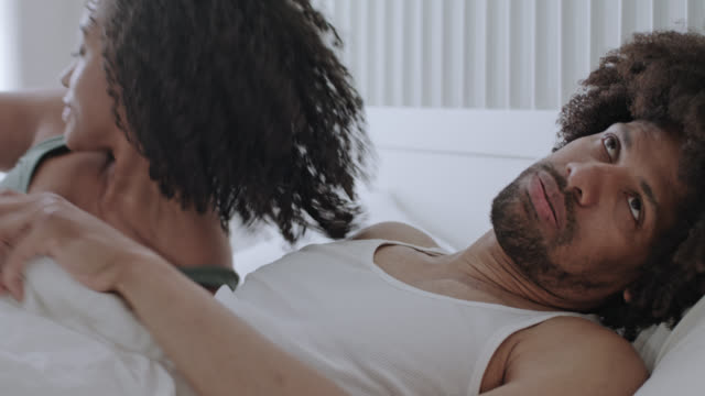 mid adult dark-skinned love couple happy together at home in white bed on a weekend - she persuades him to get out of bed while he's bugged getting up. - getting out stock videos & royalty-free footage