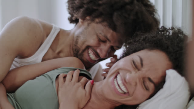 stockvideo's en b-roll-footage met mid adult dark-skinned love couple having great fun together in white bed on a free weekend. - dubbel bed