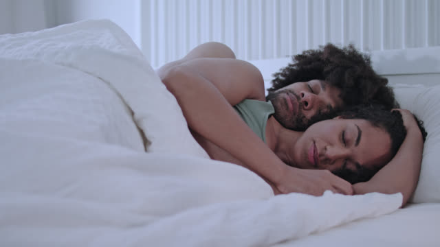 stockvideo's en b-roll-footage met mid adult dark-skinned love couple sleeping and dreaming embraced together peaceful in white hotel bed. - dubbel bed