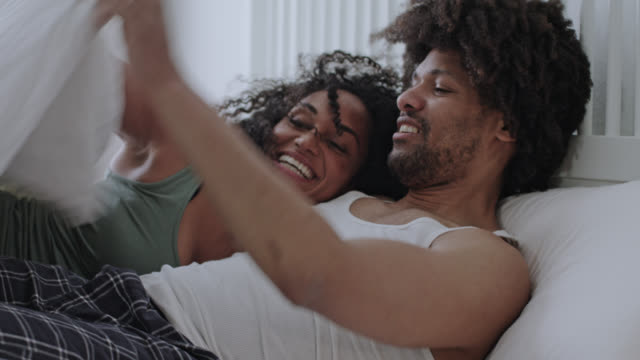stockvideo's en b-roll-footage met mid adult dark-skinned love couple together at home happy staying in bed on a day off weekend - jumping on white bed and covering up with duvet blanket while having great fun. - dubbel bed