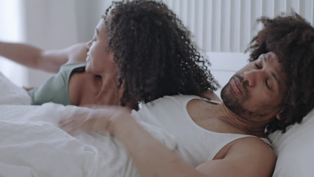 stockvideo's en b-roll-footage met mid adult dark-skinned love couple together at home in a white bed on a weekend, she the power woman makes him getting out of the bed after a short night on a hangover morning. - dubbel bed