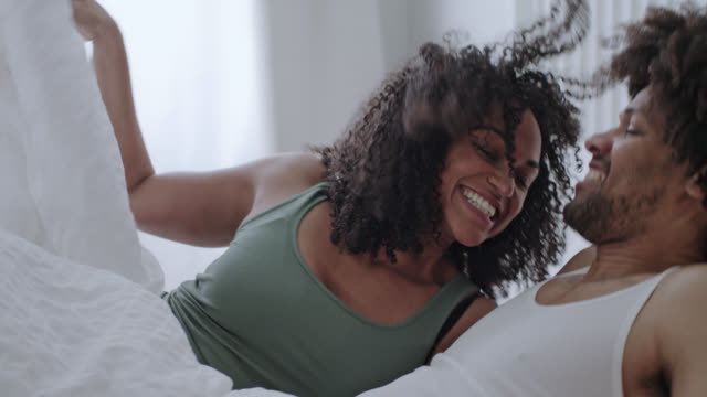 vidéos et rushes de mid adult dark-skinned positive and happy love couple together at home on a day off weekend - jumping on white bed and enjoying themselves. - pyjama