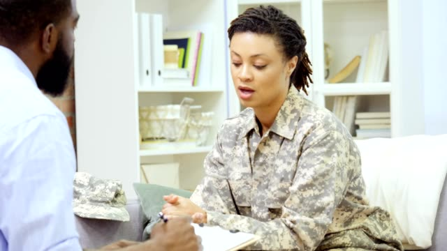mid adult female army veteran discusses something with therapist - war veteran stock videos & royalty-free footage