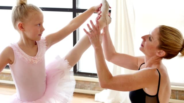 Mid adult female ballet teacher helps a young student with ballet pose