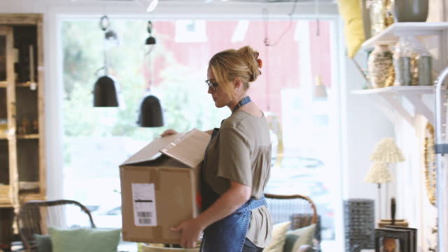 vidéos et rushes de mid adult female entrepreneur unpacking cardboard box in store - carrying