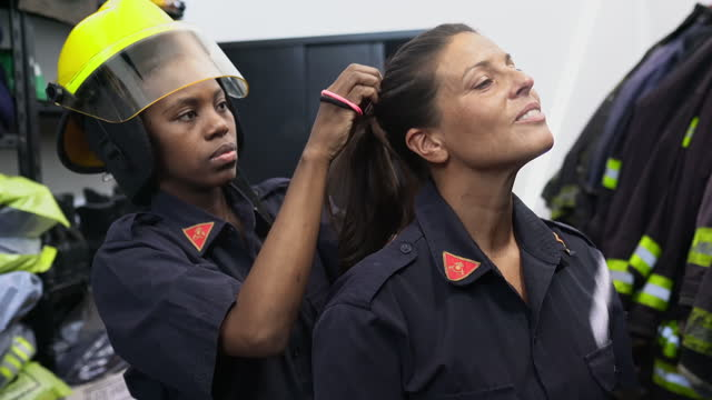 mid adult female firefighters preparing for emergency gear - fire station stock videos & royalty-free footage