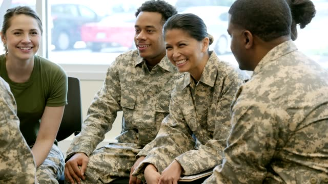 mid adult female soldier discusses something with soldier friends - war veteran stock videos & royalty-free footage