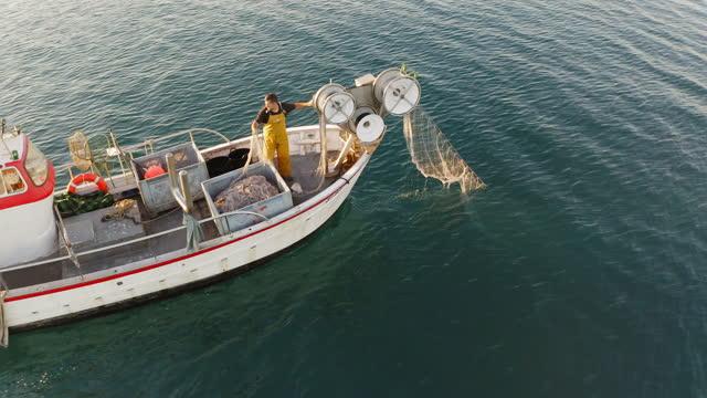 mid adult fisherman reeling in trawl net - fisherman stock videos & royalty-free footage