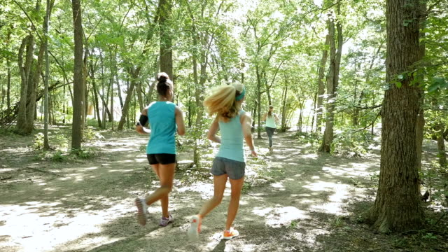 mid adult fitness instructor leading off road running club during jog outdoors - people in a row stock videos and b-roll footage