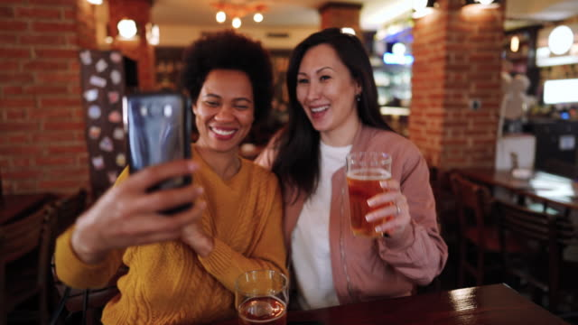 mid adult friends in pub taking selfie - moving activity stock videos & royalty-free footage