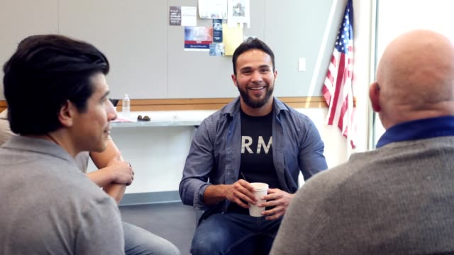 mid adult hispanic army veteran shares an experience during support group meeting - centro sociale video stock e b–roll