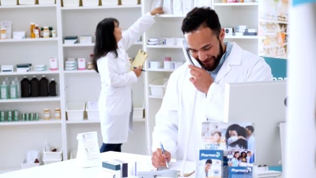 mid adult hispanic male pharmacist talks to customer on the telephone - doctor multitasking stock videos & royalty-free footage