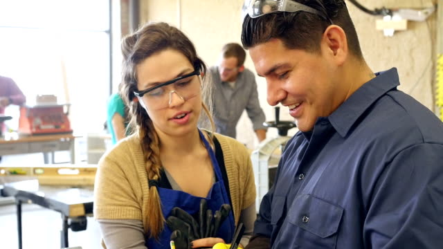 Mid adult Hispanic man and young Hispanic woman discuss project in woodshop