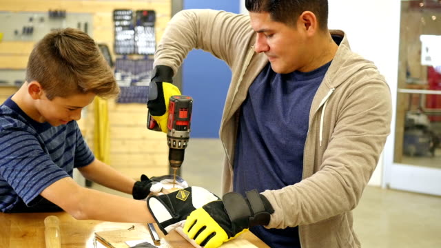 mid adult hispanic man teaches hispanic preteen boy how to drill a hole in board - drill instructor stock videos & royalty-free footage