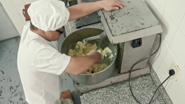 mid adult hispanic pasta maker operating machinery in factory - dough stock videos & royalty-free footage