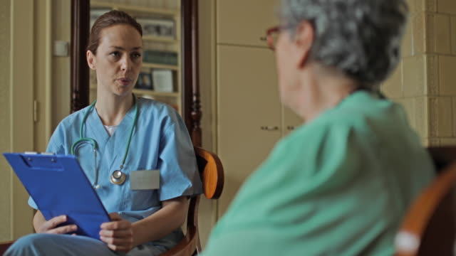 mid adult home caregiver talking to senior woman during the visit. - female nurse stock videos and b-roll footage