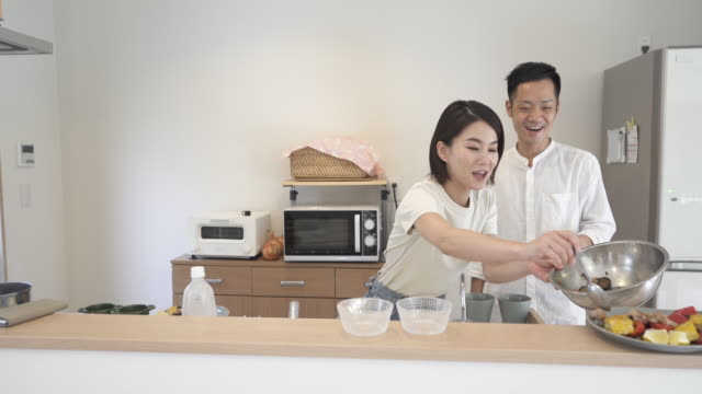 mid adult japanese couple in preparing food in the kitchen - mid adult couple stock videos & royalty-free footage