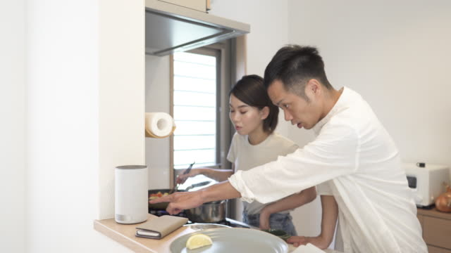 mid adult japanese couple in preparing food in the kitchen - domestic kitchen stock-videos und b-roll-filmmaterial
