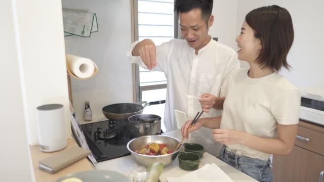 mid adult japanese couple in preparing food in the kitchen - preparing food点の映像素材/bロール