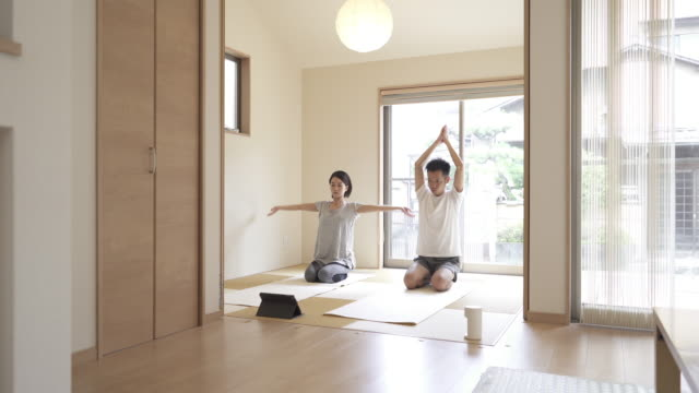 mid adult japanese couple stretching exercises with digital tablet in the japanese-style room at home. - simple living bildbanksvideor och videomaterial från bakom kulisserna