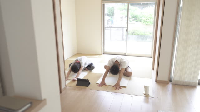 mid adult japanese couple stretching exercises with digital tablet in the japanese-style room at home. - mid adult couple stock videos & royalty-free footage