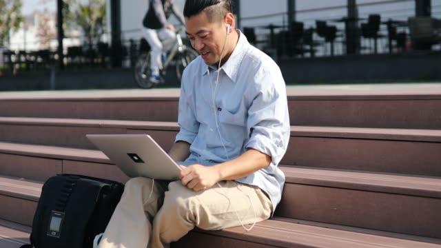 ミッドアダルト日本語はノートパソコンで働いています - 道具類点の映像素材/bロール