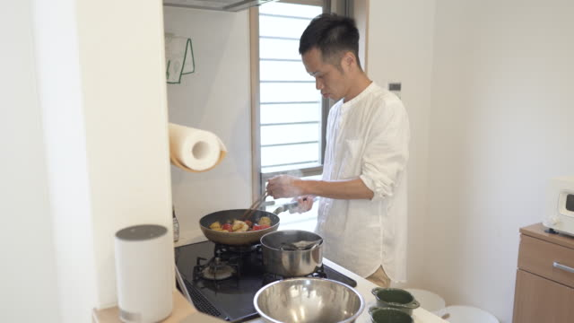 mid adult japanese man spend time cooking at home. - preparing food点の映像素材/bロール
