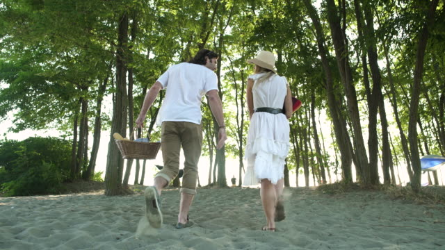 A mid adult man and a young woman walking among trees