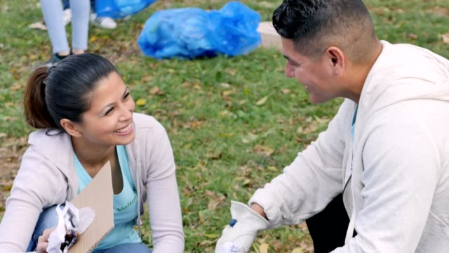 Mid adult man and woman help beautify their community with their neighbors