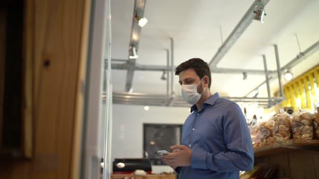 vidéos et rushes de homme adulte moyen achetant avec le masque de visage au magasin - col blanc