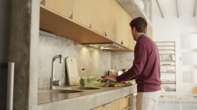 Mid adult man cooking food at kitchen counter