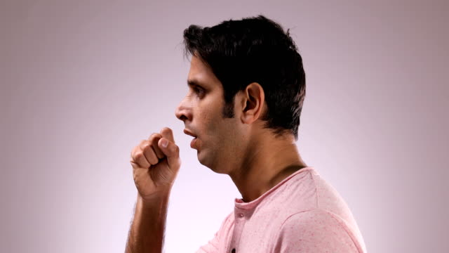 vídeos y material grabado en eventos de stock de cu mid adult man coughing while standing against pink background / new delhi, delhi, india - vista de costado