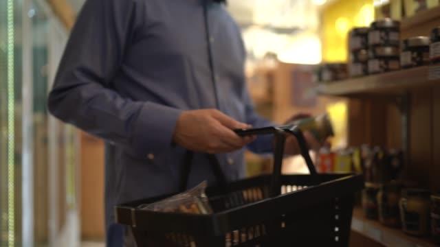 vídeos de stock, filmes e b-roll de cliente de homem adulto médio comprando em supermercado - escolher