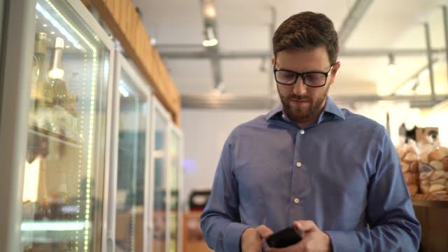 vídeos y material grabado en eventos de stock de medio adulto hombre cliente comprando usando el teléfono móvil en la tienda - pasillo objeto fabricado