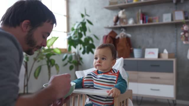 mittlere erwachsene mann fütterung baby junge am morgen zu hause - single father stock-videos und b-roll-filmmaterial