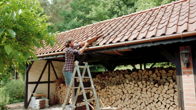 mid adult man fix roof tile - roof tile stock videos & royalty-free footage