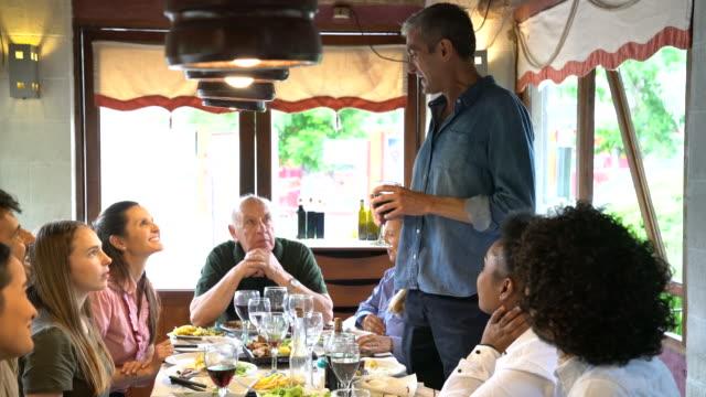 vídeos de stock e filmes b-roll de mid adult man giving speech to family in restaurant - discurso