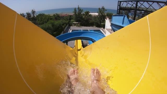 vídeos de stock e filmes b-roll de mid adult man having fun on a waterslide - escorrega de água